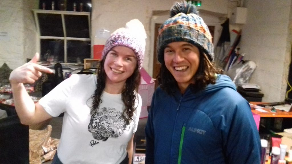 A girl with a white t-shirt with a logo on a brain on. She is stood next to a man who's last name is Brain. Both are wearing excellent bobble hats.