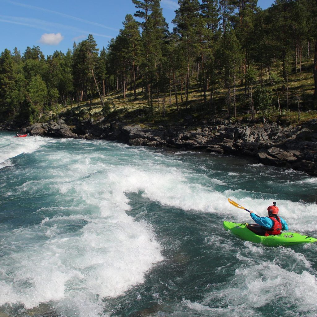 A girl in a green kayak paddling down a river. She is about to hit a wave train.