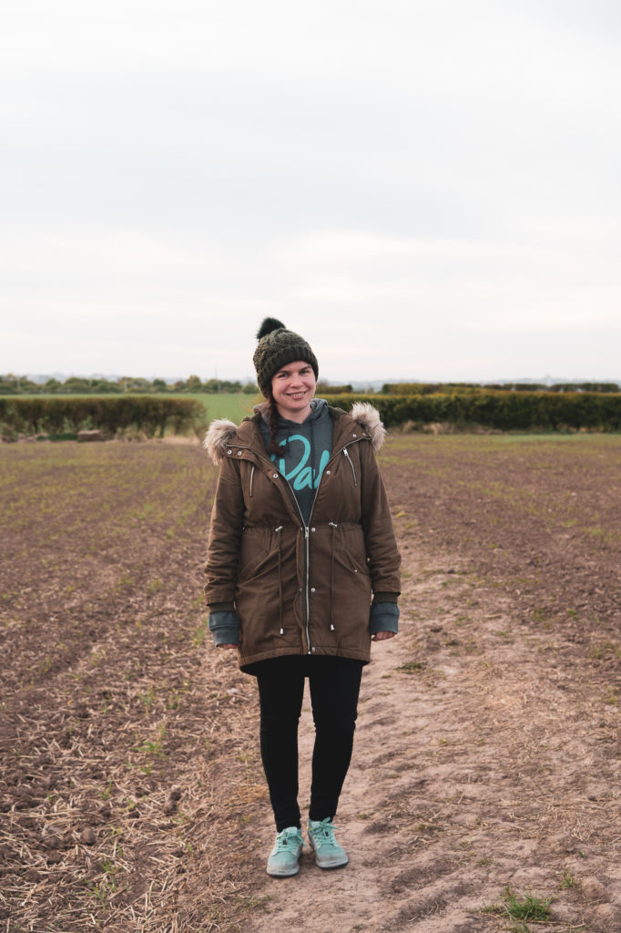 A girl stood in a field at dusk , wearing a dark green coat and black jeans.
