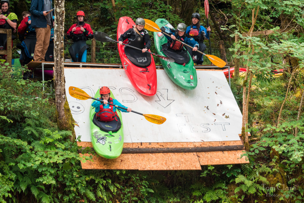 Three female kayakers are falling down a ramp located above a river. A woman in a green kayak is in front with two other women in red and green kayaks behind her.