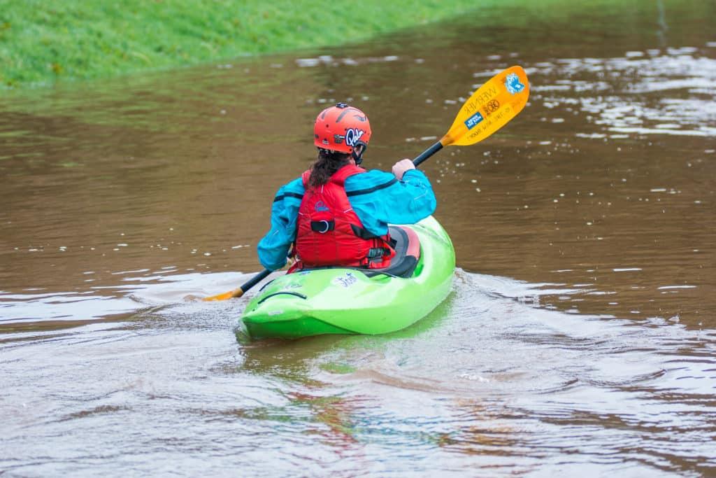 A girl paddles in a green Waka kayak on a flat lake.