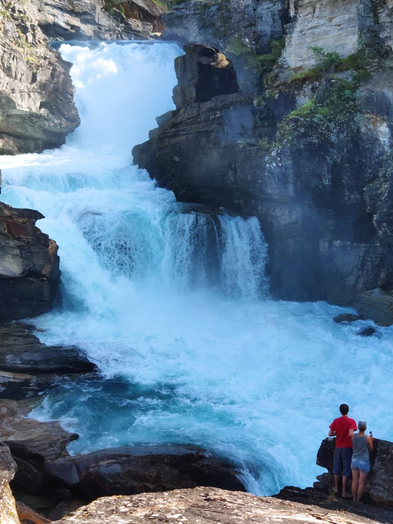 An impressive waterfall. At the bottom, two people stand facing it. They are small in comparison.