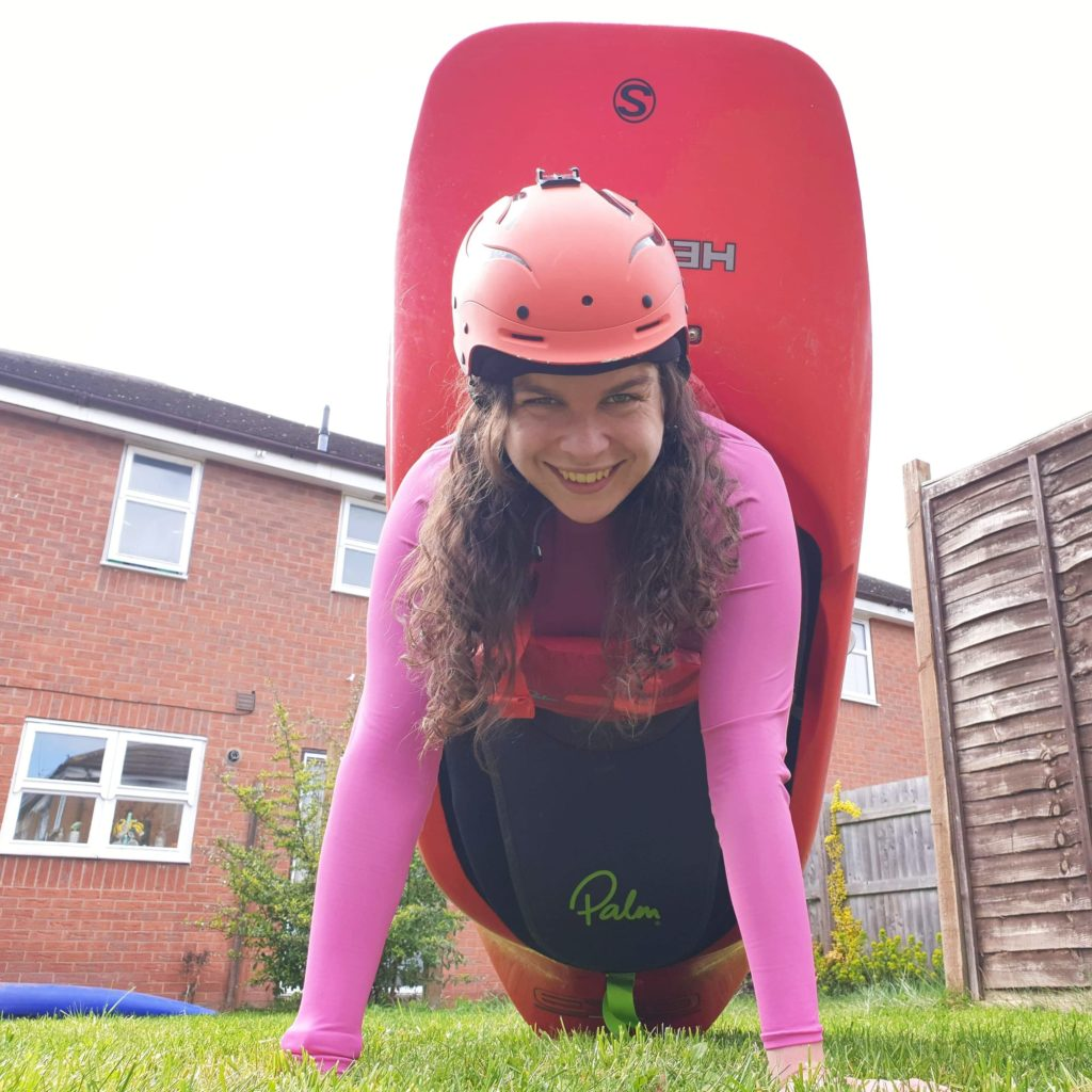 A girl is sitting in a red playboat in her garden. She has pushed the boat onto its end and is supporting herself with her arms in a press up position.
