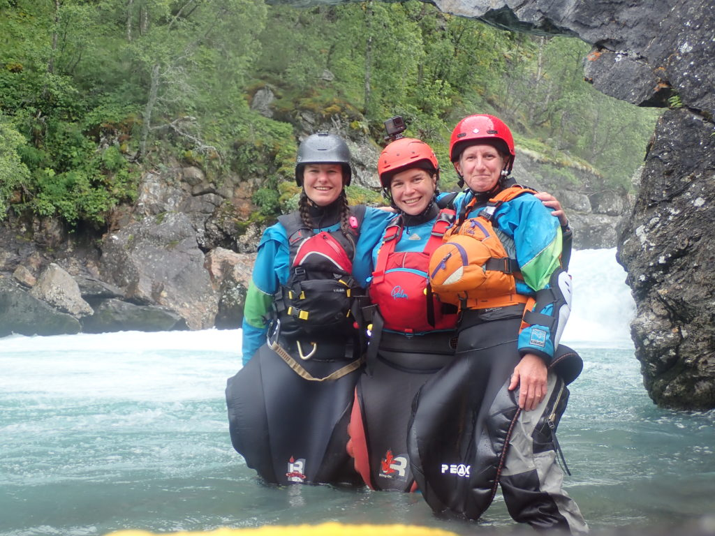 Three females kayakers stand below a drop. They are knee deep in the water and smiling.