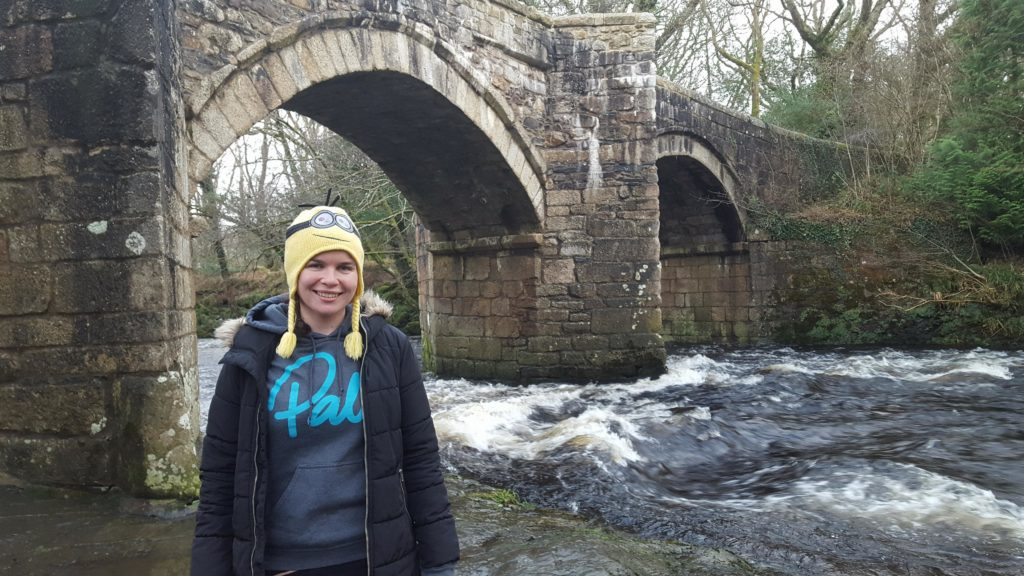 Girl standing by a bridge with whitewater underneath it. The girl is wearing a yellow minion hat and a hoody that says Palm.