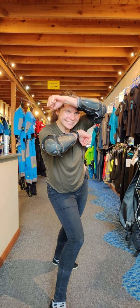 A woman standing in a kayaking shop. She is wearing elbow pads and is standing in a warrior pose.
