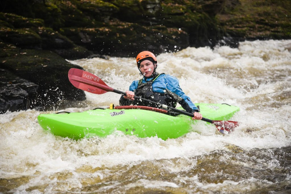A girl in a green Waka kayak paddles down a whitewater rapid. She is wearing a blue drysuit and an orange helmet.