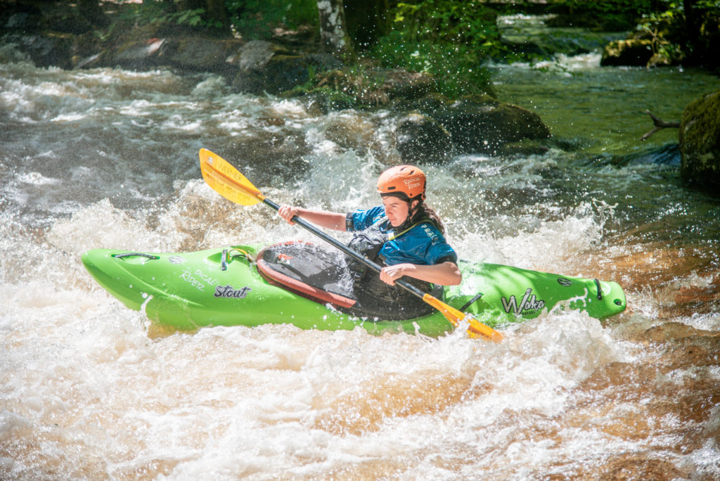 The same girl in the same green kayak. She is paddling a different rapid and it is very sunny.