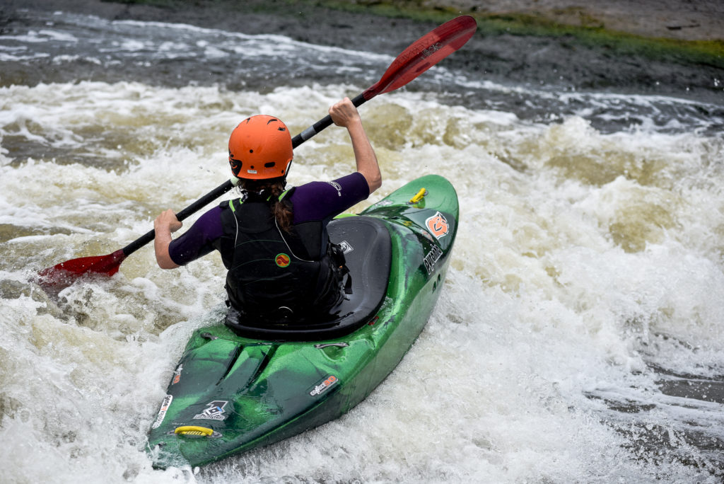 A girl surfs a hole at a white water course. The camera is from behind her and she is in a small dark green Z.One, a black BA and orange helmet.
