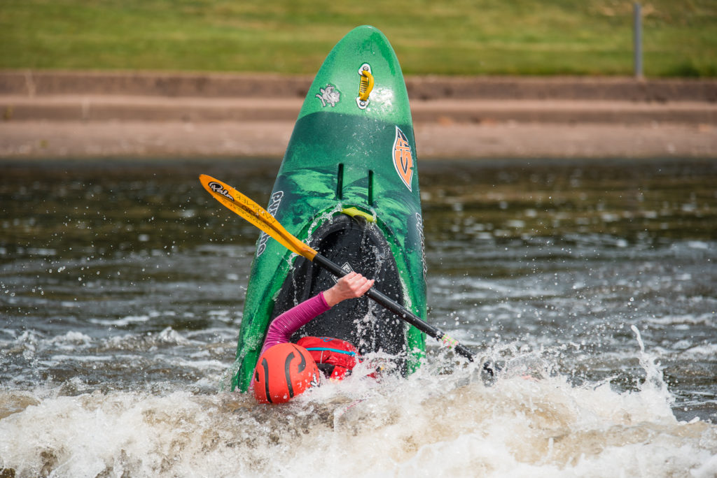 A girl is in her dark green kayak and the boat is vertical in the water. Her orange helmet is just seen above the water and her yellow paddles are helping her to direct the boat.